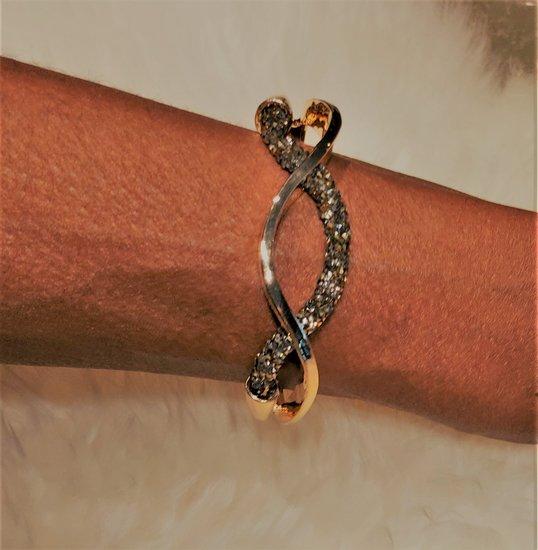 Gouden design armband met zwarte strass.