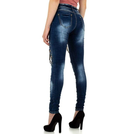Trendy destroyed blue jeans met versiering.