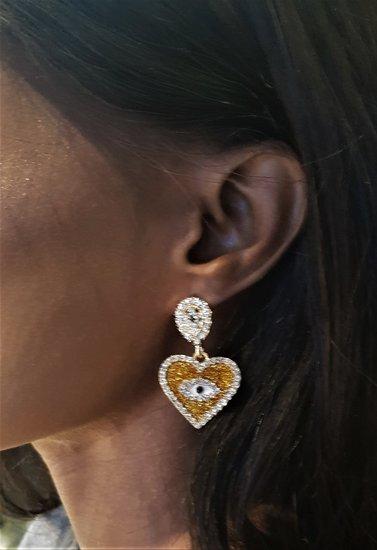 Gele oorbellen in hartvorm met oog en strass.