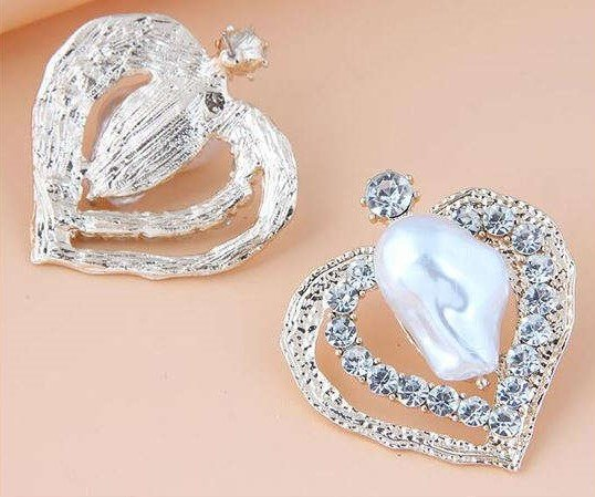 Witte hartvormige oorbellen met onregelmatige parel.
